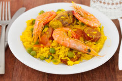Paella on white plate and glass Stock Photos