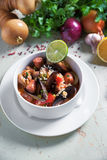 Paella in white plate with saffron rice, peas, shrimps, mussels, squid, meat. Seafood paella, traditional spanish dish. Stock Photos