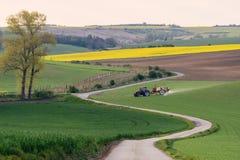 Paesaggio agricolo con il trattore che ara un campo marrone a strisce Fotografia Stock