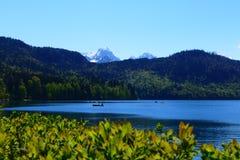 Paesaggio alpino con la gente in barche fotografia stock libera da diritti