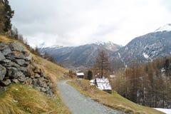 Paesaggio alpino con la strada non asfaltata lungo il pendio di montagna fotografia stock libera da diritti