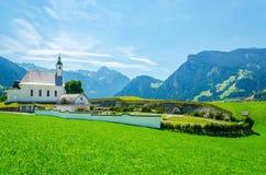 Paesaggio alpino con le alpi tipiche dell'austriaco della chiesa Fotografia Stock