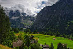 Paesaggio alpino con le montagne coperte dalle nuvole in Grindelwald, Svizzera Fotografia Stock Libera da Diritti