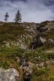 Paesaggio alpino della montagna con la cascata e le nuvole Fotografie Stock