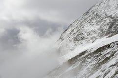 Paesaggio alpino di Snowy con le montagne e le nuvole Fotografia Stock