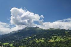 Paesaggio alpino scenico con le montagne foresta e case Fotografia Stock