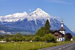 Paesaggio alpino Svizzera di estate con i picchi della neve e le costruzioni di legno Immagini Stock