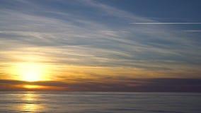 Paesaggio arancio di tramonto della fiamma con il sole riflesso nell'acqua video d archivio