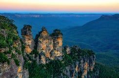 Paesaggio australiano stupefacente e tre sorelle formazione rocciosa nelle montagne blu al tramonto Fotografia Stock Libera da Diritti