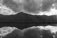 Paesaggio in bianco e nero della montagna con la riflessione del lago e le nuvole drammatiche Immagine Stock Libera da Diritti