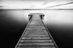 Paesaggio in bianco e nero Passaggio pedonale di legno nel mare e superficie di acqua liscia Immagine Stock