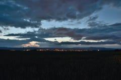 Paesaggio ceco di notte con il campo in priorità alta e città di Chomutov con le montagne del minerale metallifero su fondo nel g Immagini Stock