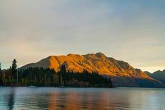 Paesaggio colorato dalla riflessione dorata del tramonto, punto di riferimento di autunno della montagna di Cecil Peak Queenstown immagini stock libere da diritti