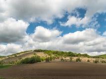 Paesaggio con i campi di agricoltura e le aree verdi su Sunny Day con il cielo nuvoloso immagini stock