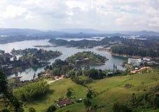 Paesaggio con i laghi calmi, le montagne verdi, le foreste fertili ed alcune ville di estate immagini stock libere da diritti