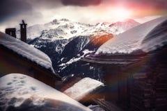 Paesaggio con i picchi di montagna e le cime del tetto del chalet coperti da Sn fotografie stock
