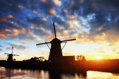 Paesaggio con il bello mulino olandese tradizionale vicino ai corsi di acqua con il tramonto e la riflessione fantastici in acqua Immagini Stock Libere da Diritti