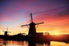 Paesaggio con il bello mulino olandese tradizionale vicino ai corsi di acqua con il tramonto e la riflessione fantastici in acqua Fotografie Stock Libere da Diritti