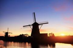Paesaggio con il bello mulino olandese tradizionale vicino ai corsi di acqua con il tramonto e la riflessione fantastici in acqua Fotografia Stock Libera da Diritti
