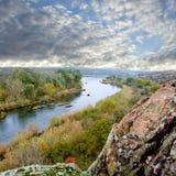 Paesaggio con il fiume, la scogliera ed il cielo immagine stock