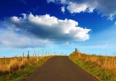 Paesaggio con il giacimento della strada e le grandi nuvole Immagine Stock Libera da Diritti