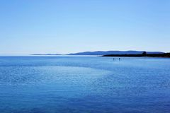 Paesaggio con il mare, montagne e stare sulle pagaie immagini stock libere da diritti