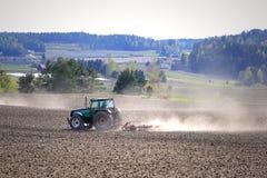 Paesaggio con il trattore agricolo che coltiva campo Fotografia Stock