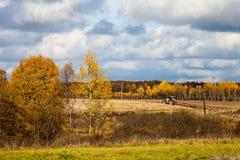 Paesaggio con l'aratura del trattore Fotografia Stock