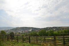 Paesaggio con la chiesa del villaggio ed il recinto di legno Immagine Stock