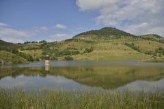 Paesaggio con la collina riflessa nel lago Immagine Stock