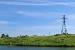 Paesaggio con la fila dei pali elettrici sopra il fiume selvaggio attraverso il prato con il chiaro cielo fotografia stock libera da diritti