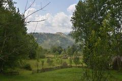 Paesaggio con la montagna, il prato ed il mucchio di fieno Fotografia Stock