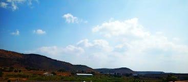 Paesaggio con la montagna, le nuvole e gli alberi fotografie stock libere da diritti