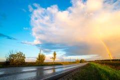Paesaggio con la strada campestre e l'arcobaleno Fotografie Stock Libere da Diritti