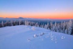 Paesaggio con le alte montagne coperte di neve Struttura congelata interessante Bella alba di inverno con cielo blu arancio Fotografie Stock Libere da Diritti