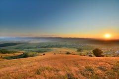 Paesaggio con le colline e i moutains al tramonto Immagini Stock