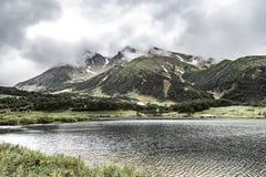 Paesaggio con le pianure verdi e lago sulla penisola di Kamchatka, Russia fotografia stock