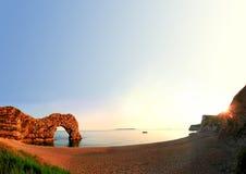Paesaggio costiero con l'arco ed il cielo blu rocciosi Fotografia Stock