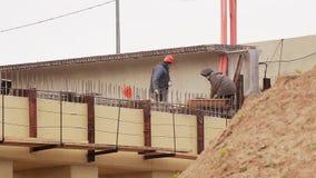 Paesaggio dei lavoratori maschii addetti all'azione al martello intorno a beem concreto archivi video