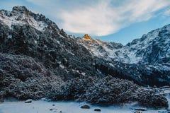 Paesaggio dei picchi innevati delle montagne rocciose in tempo soleggiato Il concetto della natura e del viaggio fotografia stock