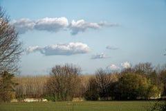 Paesaggio del campo di agricoltura, terra vuota, cielo blu e nuvole nella primavera Fotografia Stock