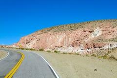 Paesaggio del deserto di Altiplano e strada asfaltata aridi Immagini Stock Libere da Diritti