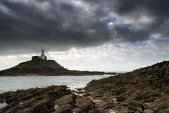 Paesaggio del faro con il cielo tempestoso sopra il mare con le rocce nella parte anteriore Immagini Stock Libere da Diritti