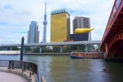 Paesaggio del fiume con un battello da diporto, torre di Tokyo Skytree, Asahi Beer Hall, ponte di Sumida fotografia stock