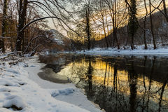 Paesaggio del fiume selvaggio con la riflessione del cielo di tramonto nelle montagne, nell'inverno Fotografia Stock Libera da Diritti