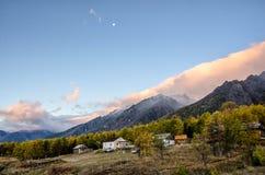 Paesaggio del lago della foresta di autunno con il cielo rosa, il villaggio e la casa di legno immagini stock