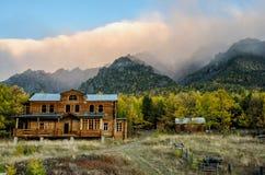 Paesaggio del lago della foresta di autunno con il cielo rosa, il villaggio e la casa di legno fotografia stock