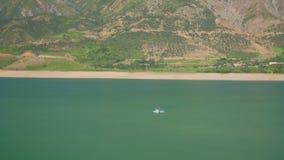 Paesaggio del lago mountain con il jet ski di galleggiamento stock footage