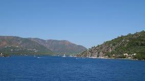 Paesaggio del mare, bella spiaggia con gli yacht su fondo delle montagne verdi di estate video d archivio