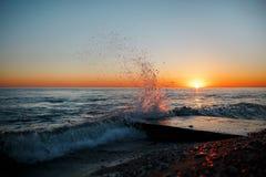 Paesaggio del mare con le onde sulla spiaggia contro il tramonto fotografie stock